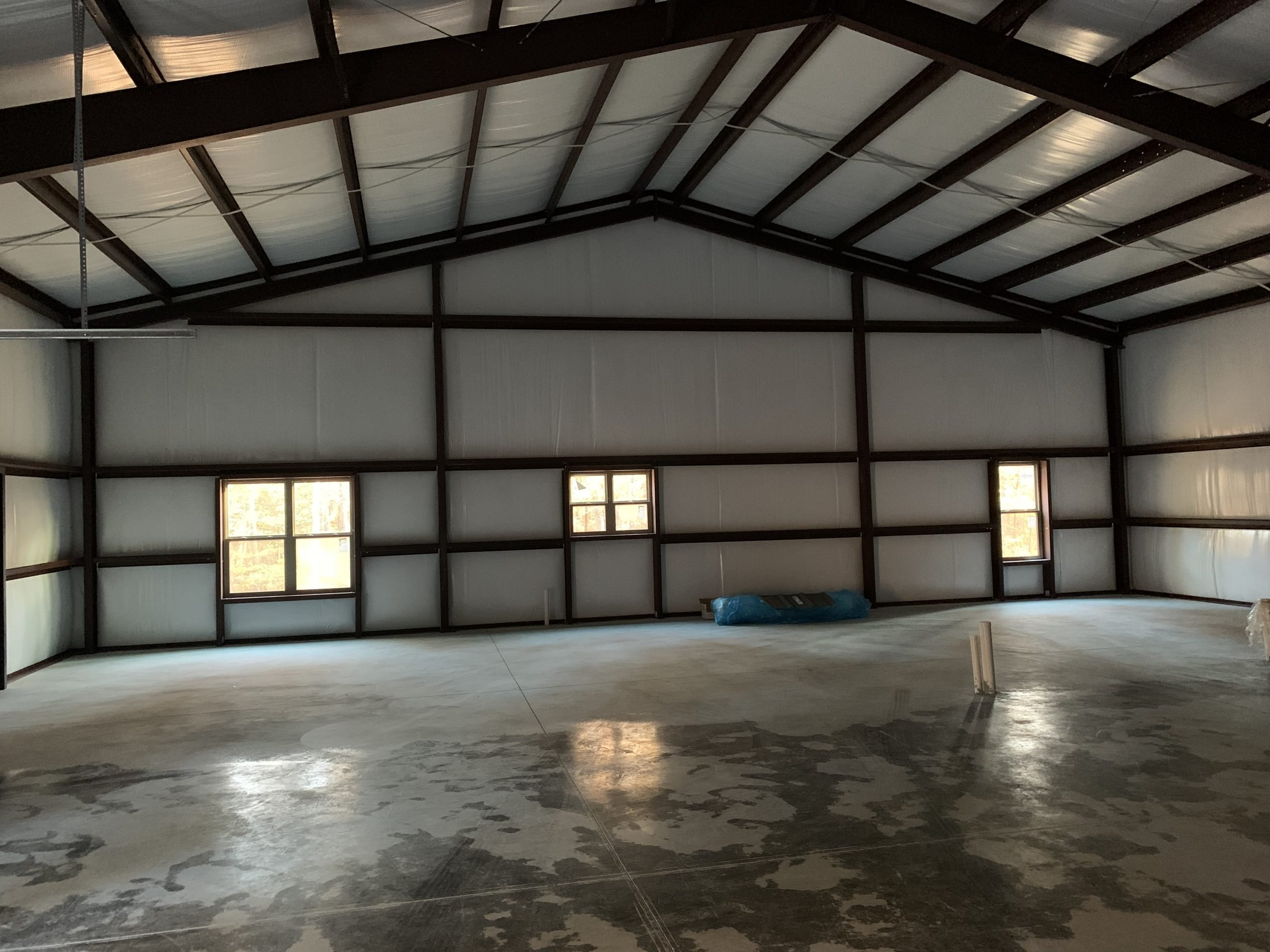 Interior View Of Pre-Engineered Metal Building With High Clearance Steel Beams And Custom Windows