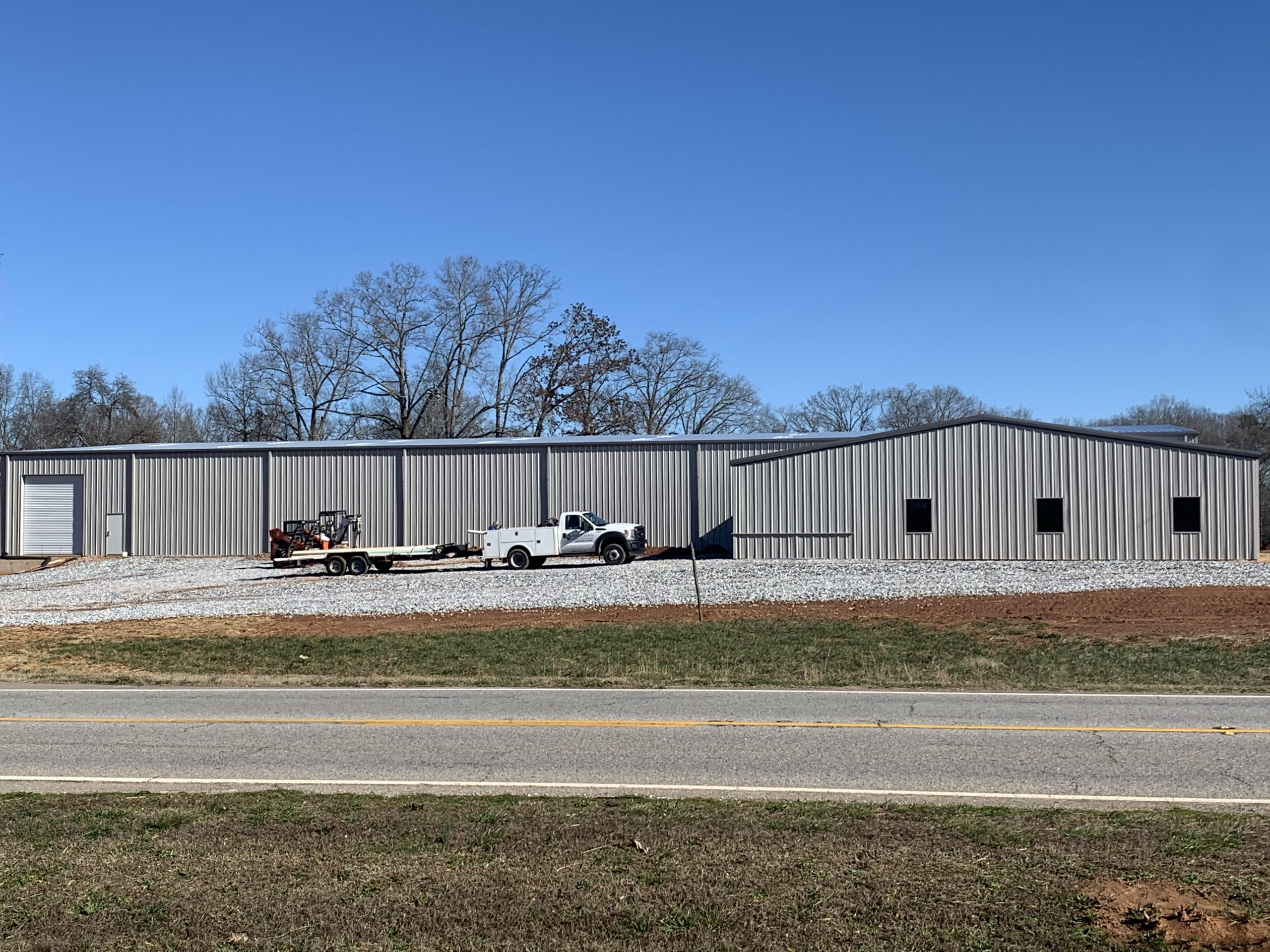 Large Custom Pre-Engineered Metal Building With Loaded Pickup Truck And Trailer Parked In Front. Custom Doors, Windows