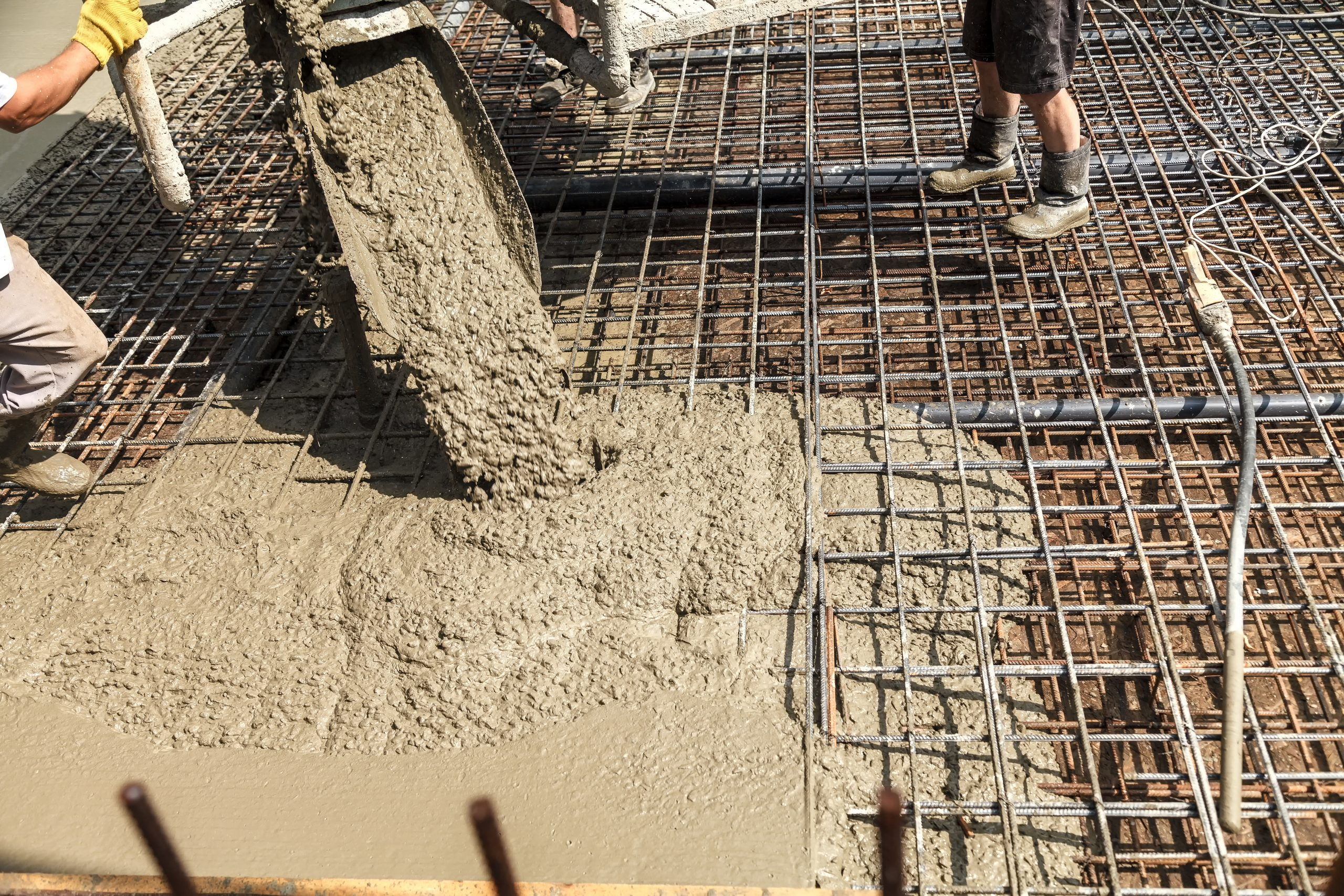 Pouring concrete for steel building foundation