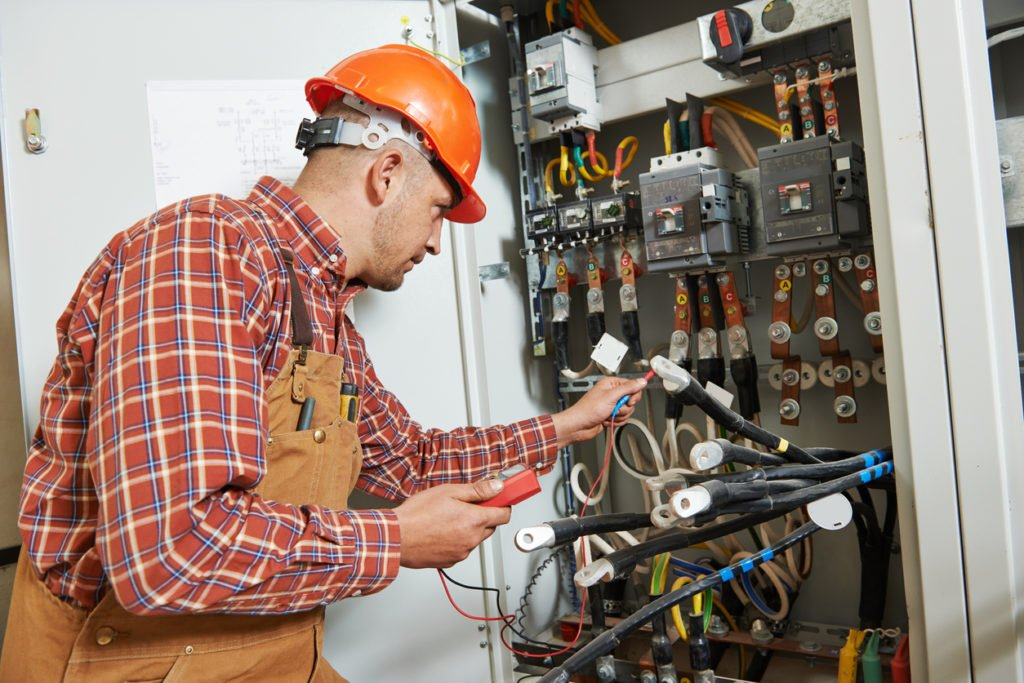 electrician installing steel building electrical switchboard