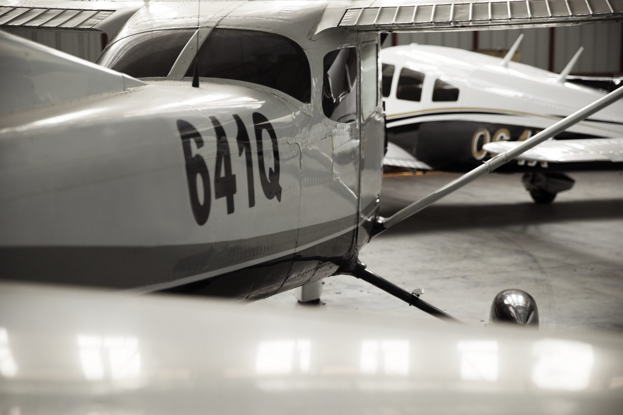 Front propellor plane parked in a metal building kit hangar